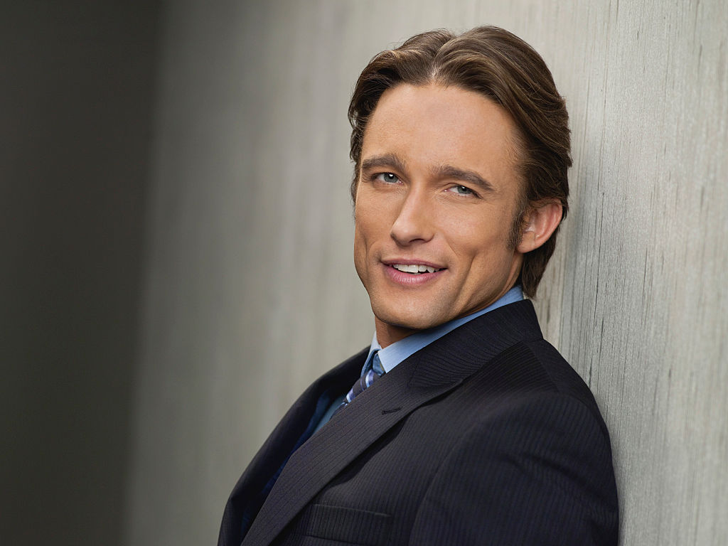 Jay Kenneth Johnson as Philip Kiriakis smiling leaning against a wall