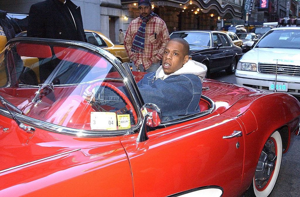 Jay-Z sitting in a red convertible