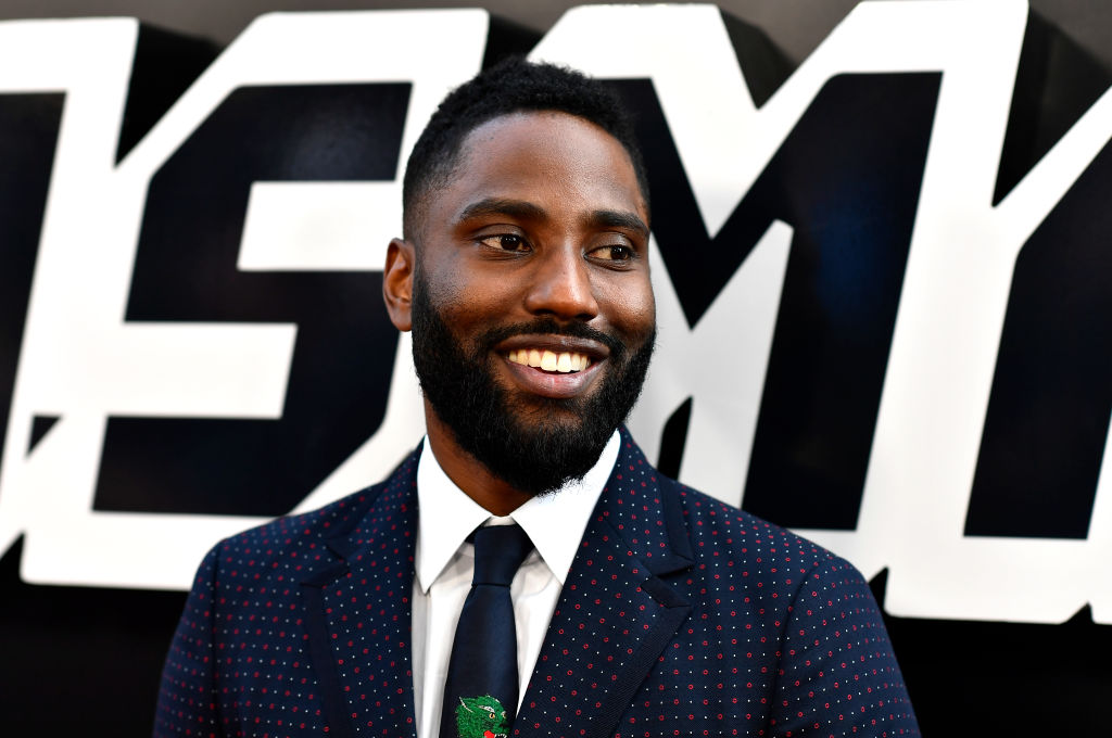 John David Washington smiling, looking away from the camera