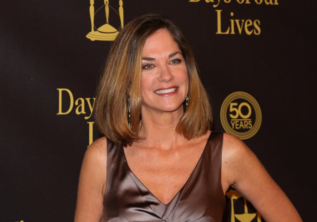 Kassie Depaiva smiling in front of a brown backdrop with the 'Days of our Lives' logo