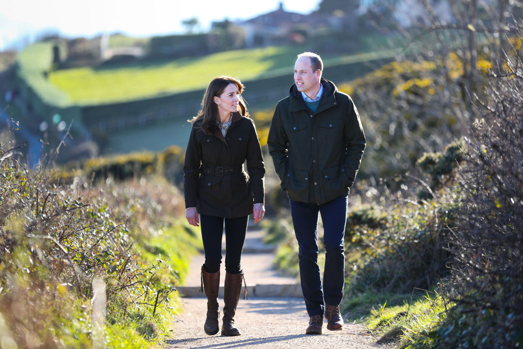 Kate Middleton and Prince William smiling, walking a dirt path surrounded by fields