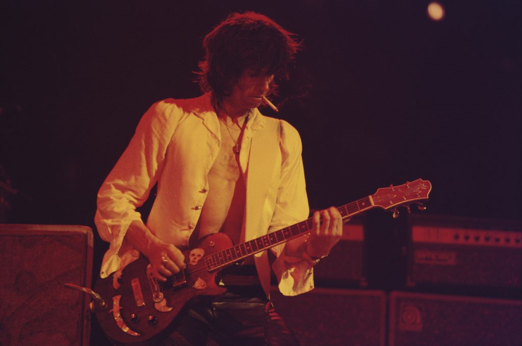 Keith Richards smoking on stage while playing guitar, looking down