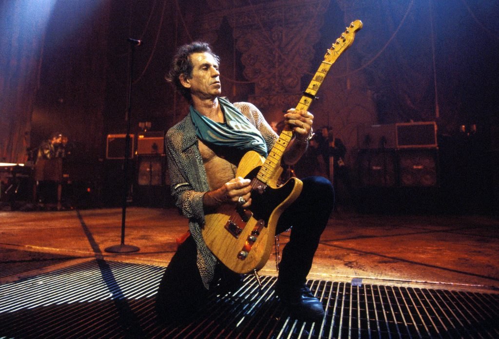 Keith Richards kneeling on stage holding a guitar, looking to the right