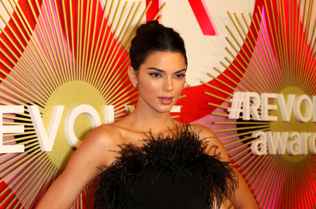 Kendall Jenner in front of a red and pink background