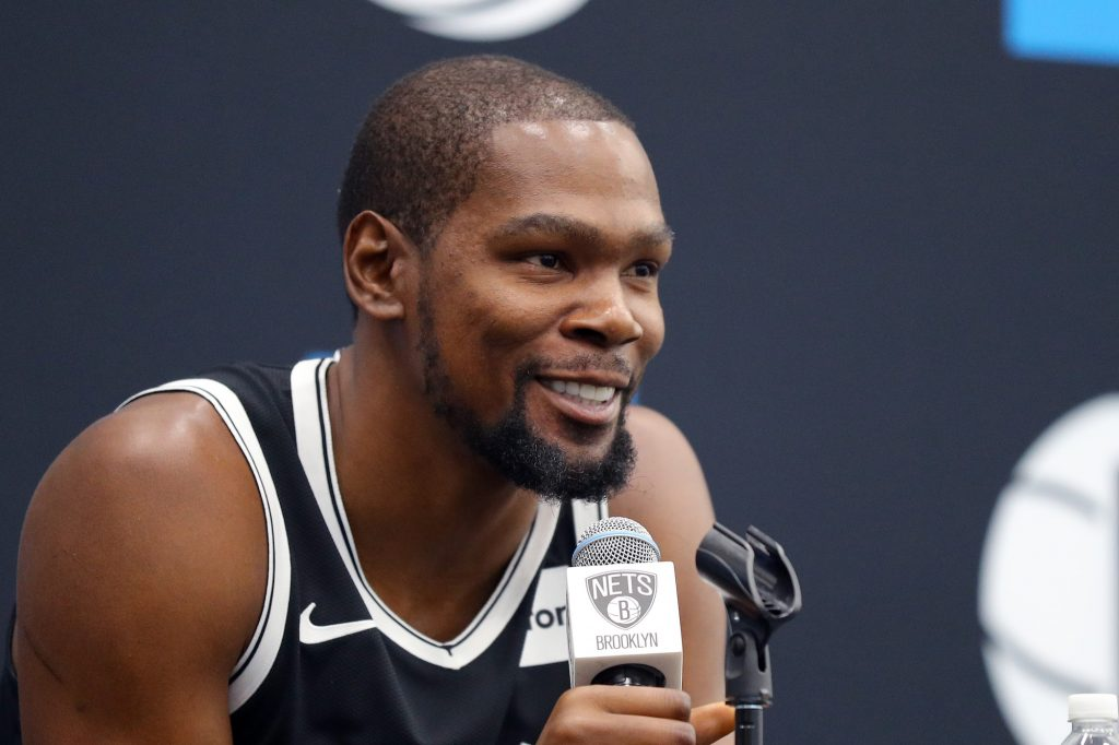 Kevin Durant smiling, holding a microphone