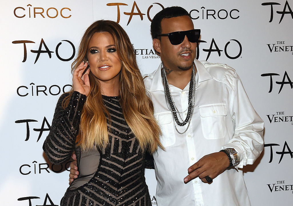 Khloé Kardashian smiling standing with French Montana in front of a white background with a repeating logo