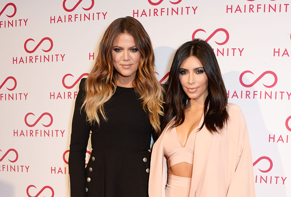 Khloé Kardashian and Kim Kardashian West smiling in front of a white backdrop with a repeating logo