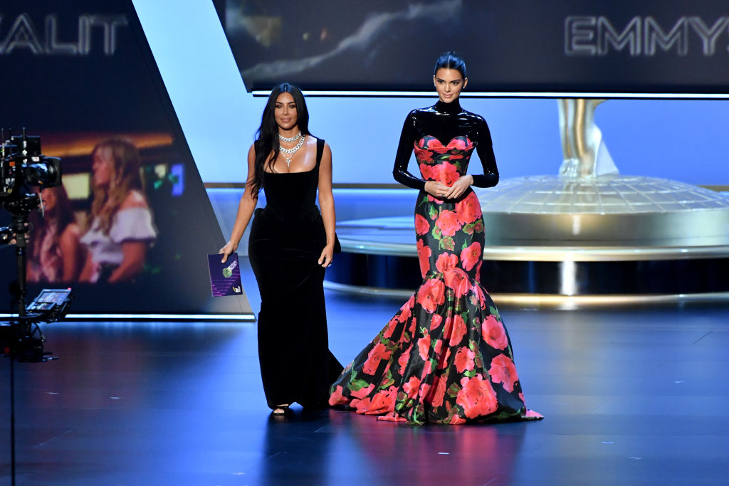 Kim Kardashian and Kendall Jenner smiling, walking on a stage