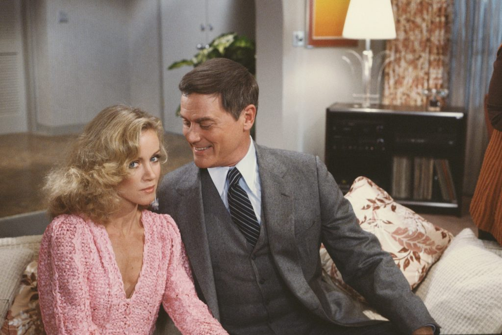 Donna Mills (as Abby Cunningham) looking at the camera, not smiling and Larry Hagman (as J.R. Ewing) smiling at Mills
