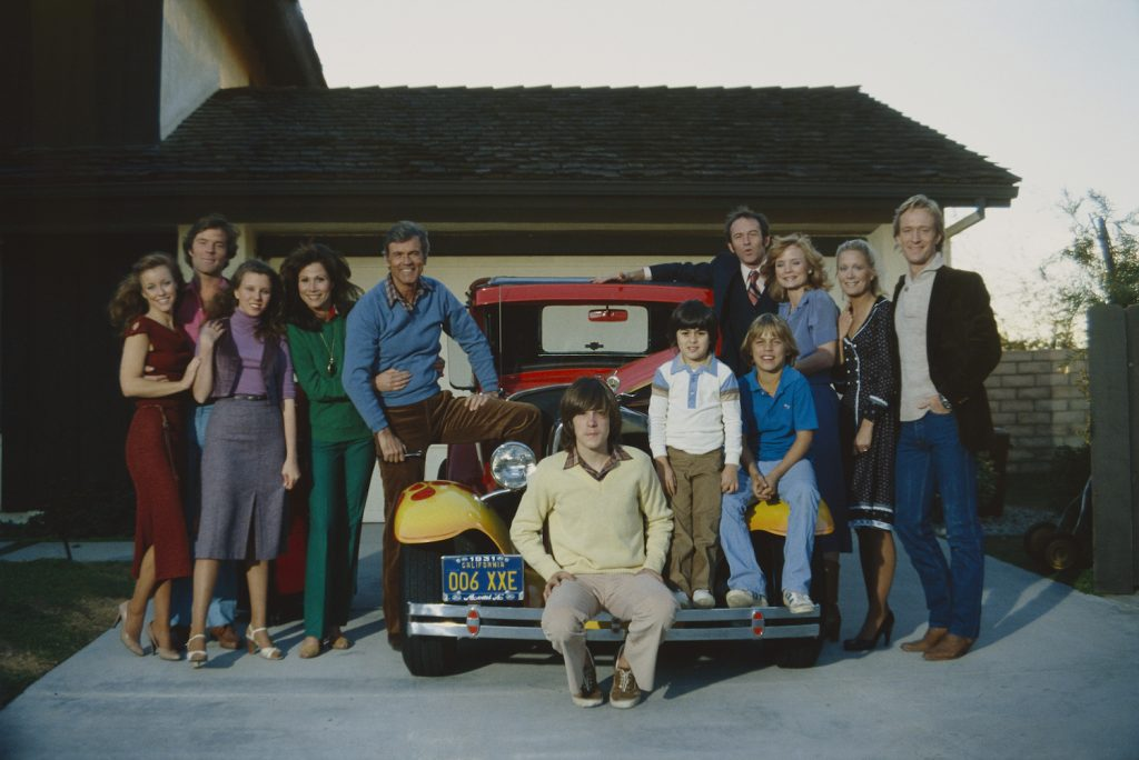 Knots Landing cast surrounding a car parked in a driveway smiling at the camera