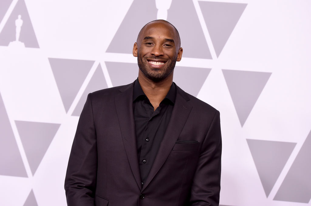Kobe Bryant smiling in front of a triangle pattern background