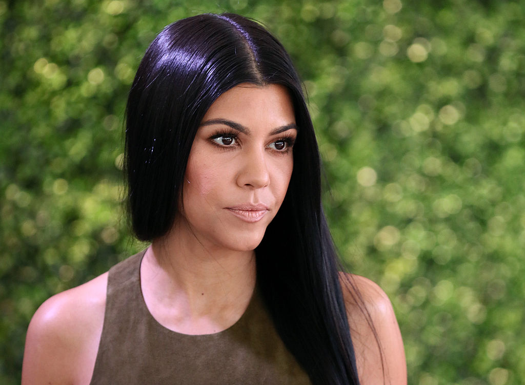 Kourtney Kardashian looking off to the side in front of a blurred green background