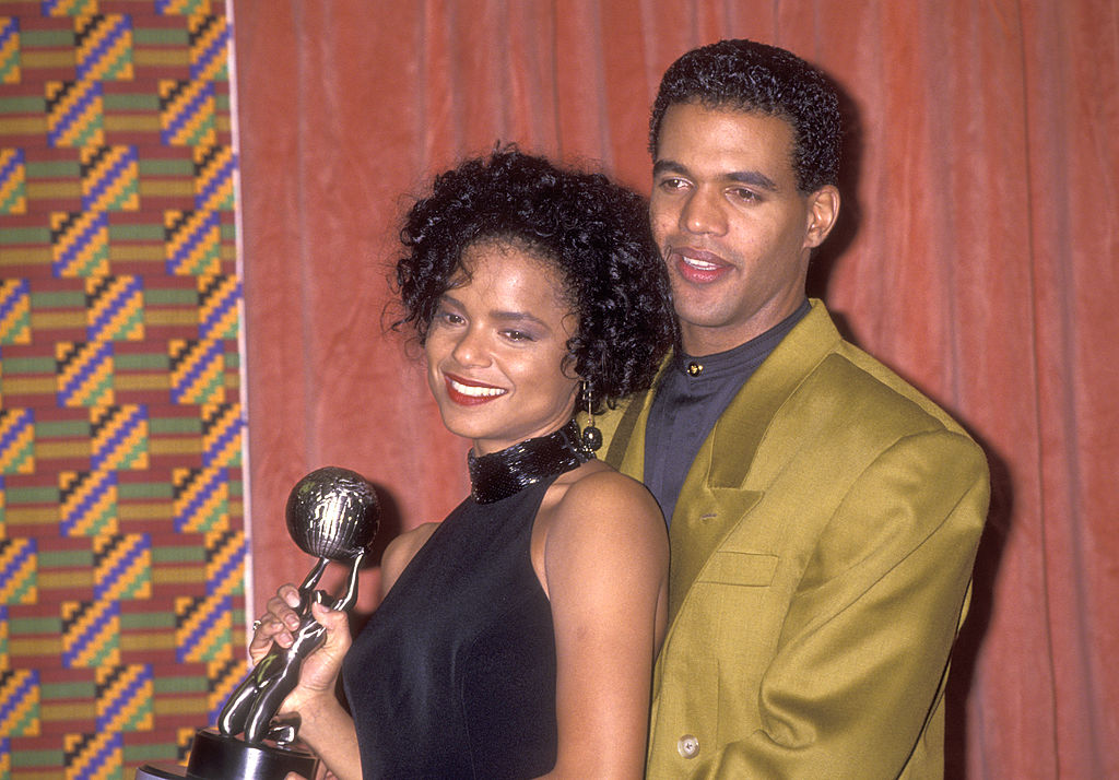 Kristoff St. John embracing Victoria Rowell, both smiling