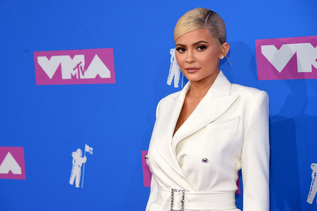 Kylie Jenner looking off camera in front of a blue background