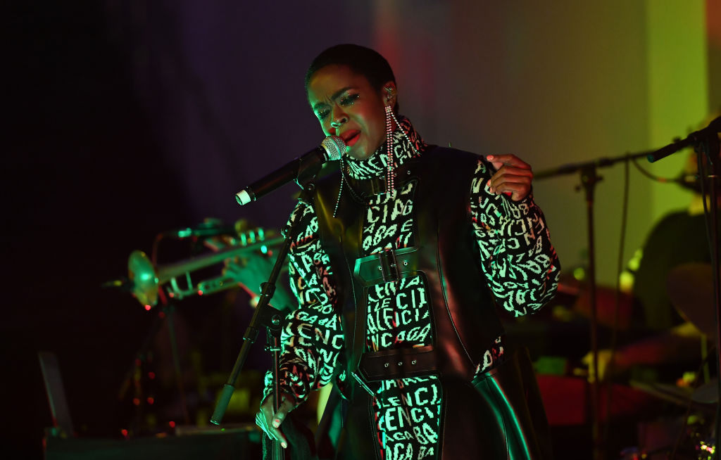 Lauryn Hill on stage singing into a microphone