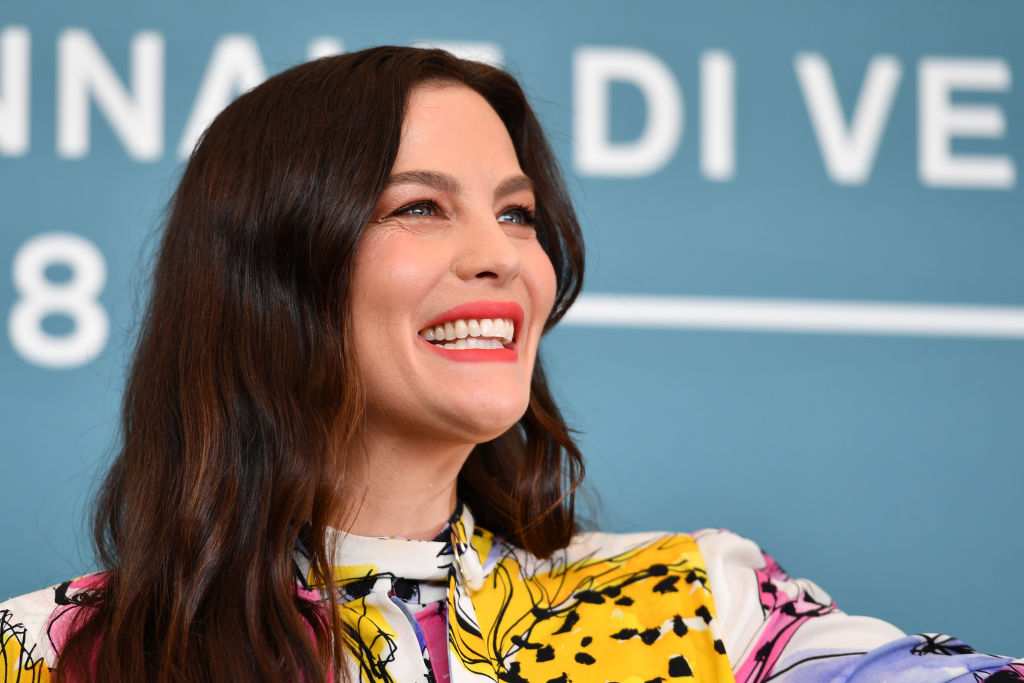 Liv Tyler smiling looking away from the camera in front of a blue background with a repeating white logo