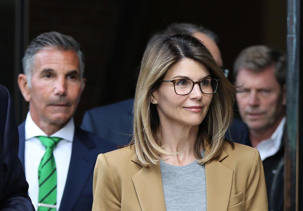 Lori Loughlin smiling wearing a blazer, walking out of a courthouse