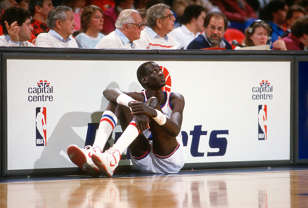 Manute Bol waiting to go into an NBA game