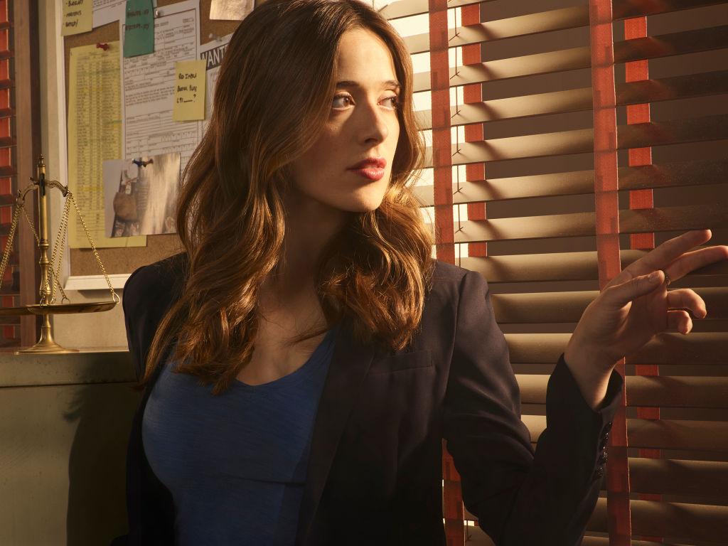 Marina Squerciati as Kim Burgess looking through blinds