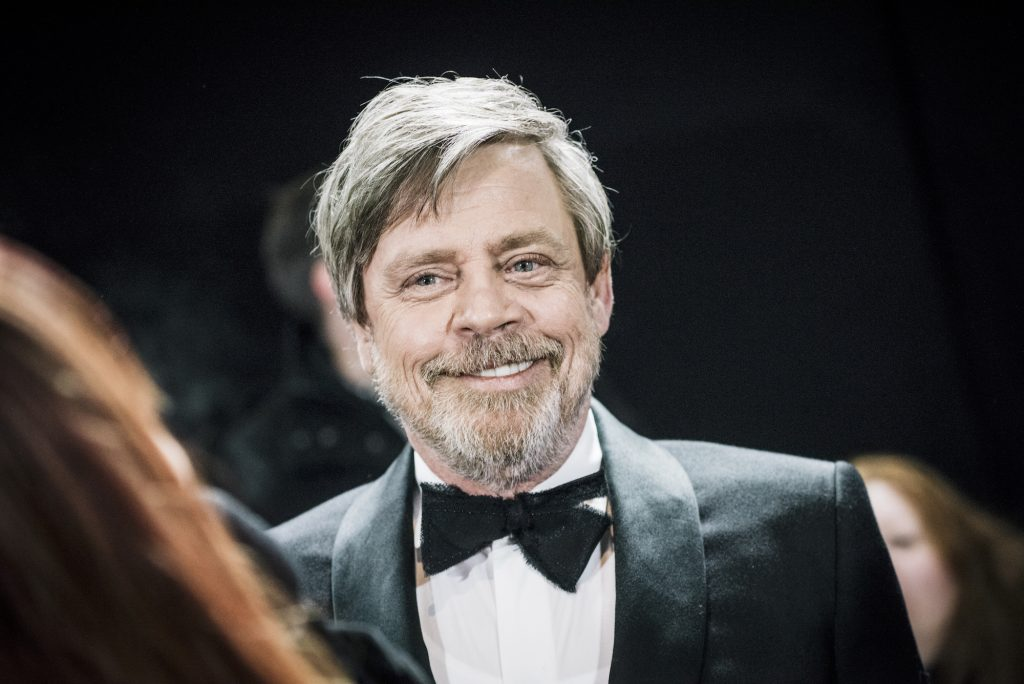 Mark Hamill smiling, wearing a suit and bowtie