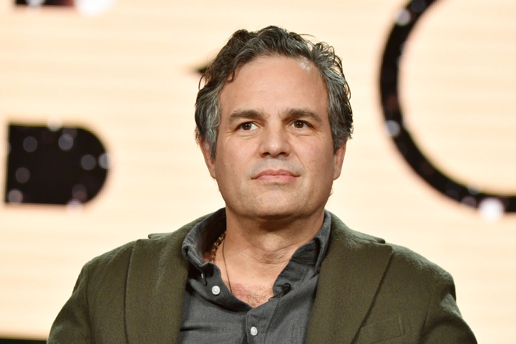 Mark Ruffalo looking off camera, not smiling, sitting down in front of a blurred background