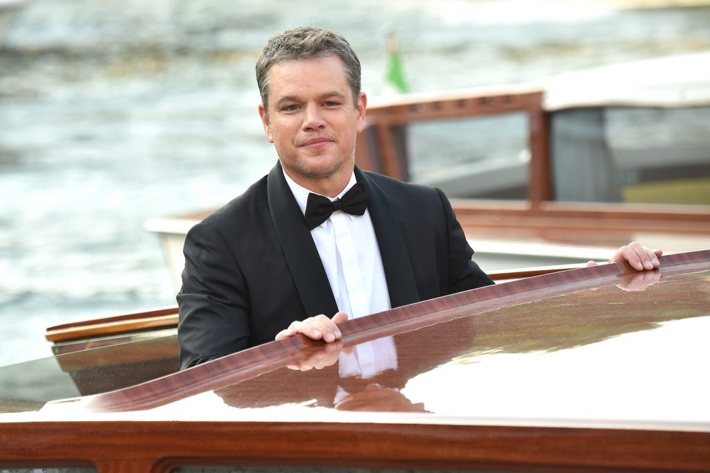 Matt Damon smiling, looking over the top of a canal bus in Venice