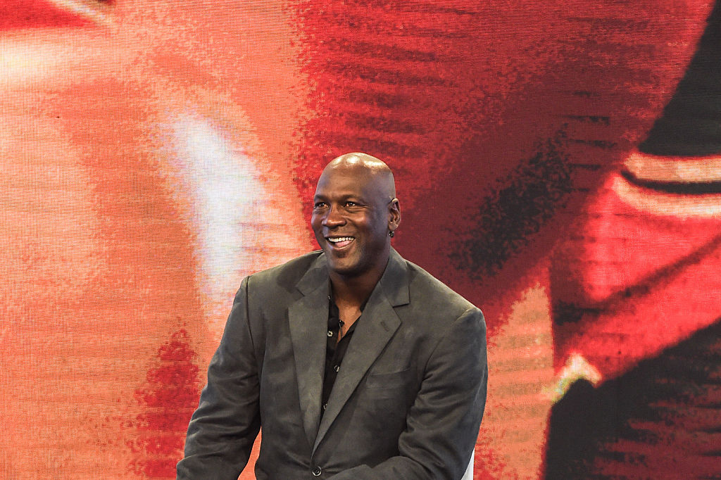 Michael Jordan smiling in front of a red background