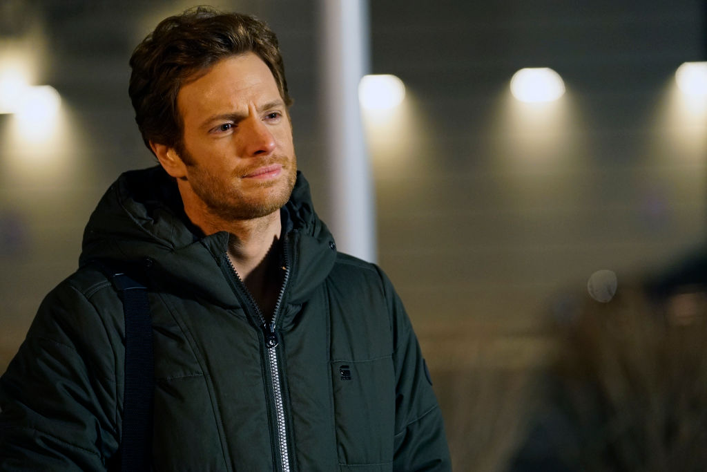 Nick Gehlfuss as Will Halstead smiling, wearing a winter jacket on set of 'Chicago Med'