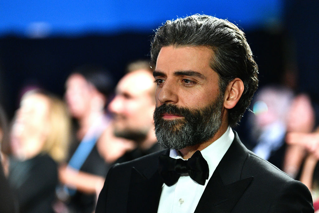 Oscar Isaac smiling slightly looking away from the camera