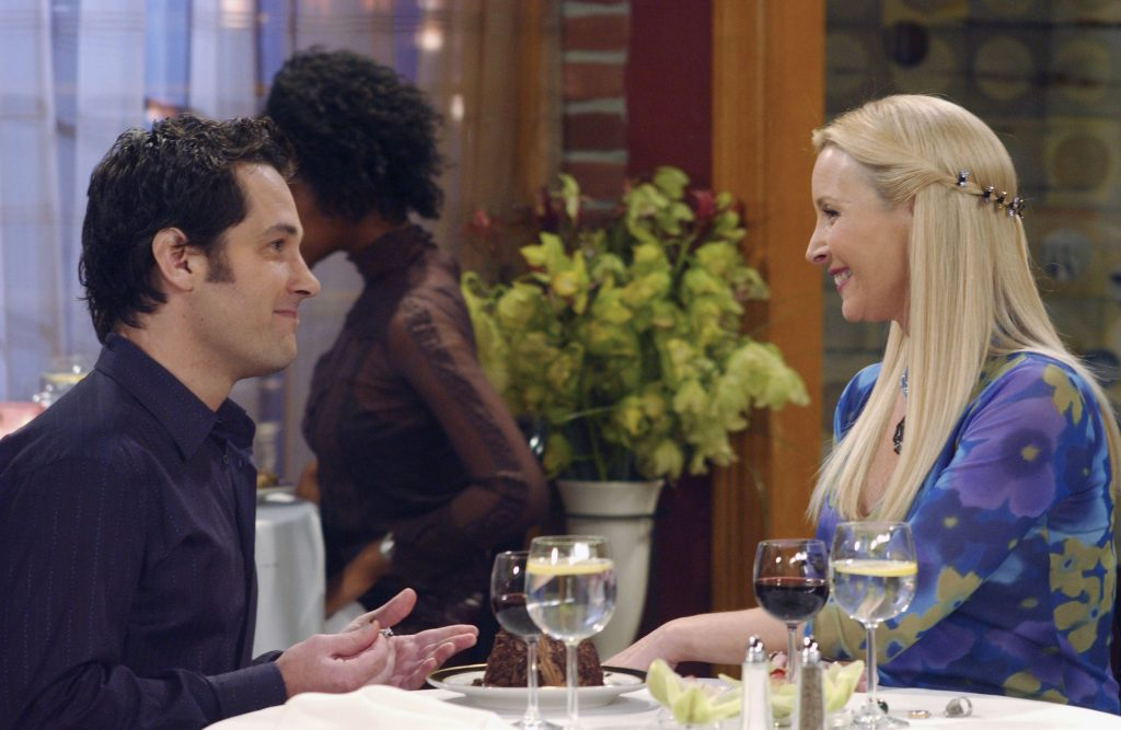 Paul Rudd as Mike Hannigan sitting at a table across from Lisa Kudrow as Phoebe Buffay in 'Friends'