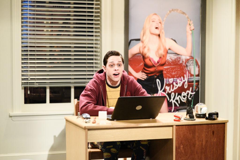 Pete Davidson on set of 'Saturday Night Live' sitting at a desk