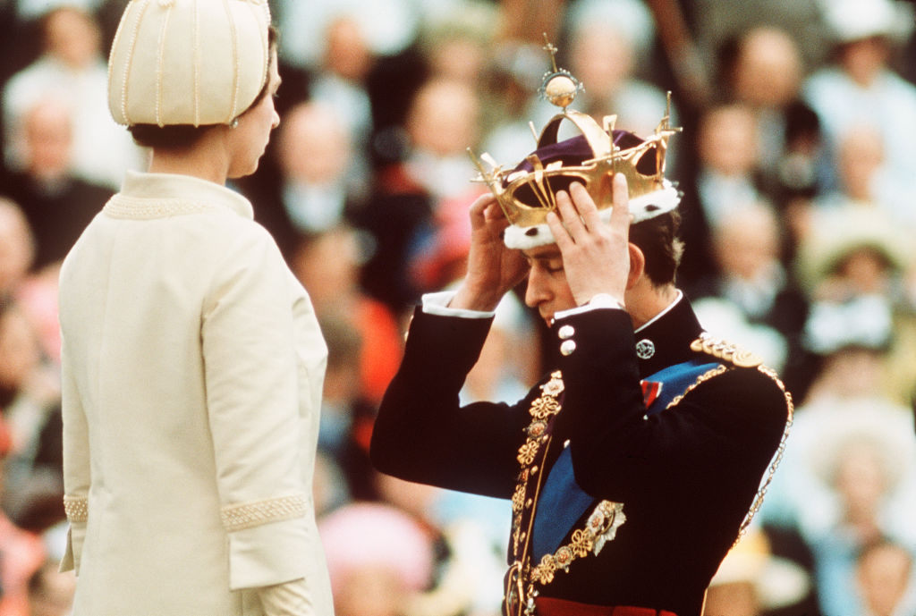 Prince Charles kneels before Queen Elizabeth as she crowns him Prince of Wales