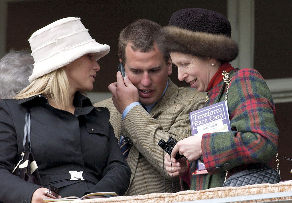 As Peter Phillips Chats On His Mobile Phone Princess Anne And Zara Phillips Move In Close To Listen At The National Hunt Festival At Cheltenham Races