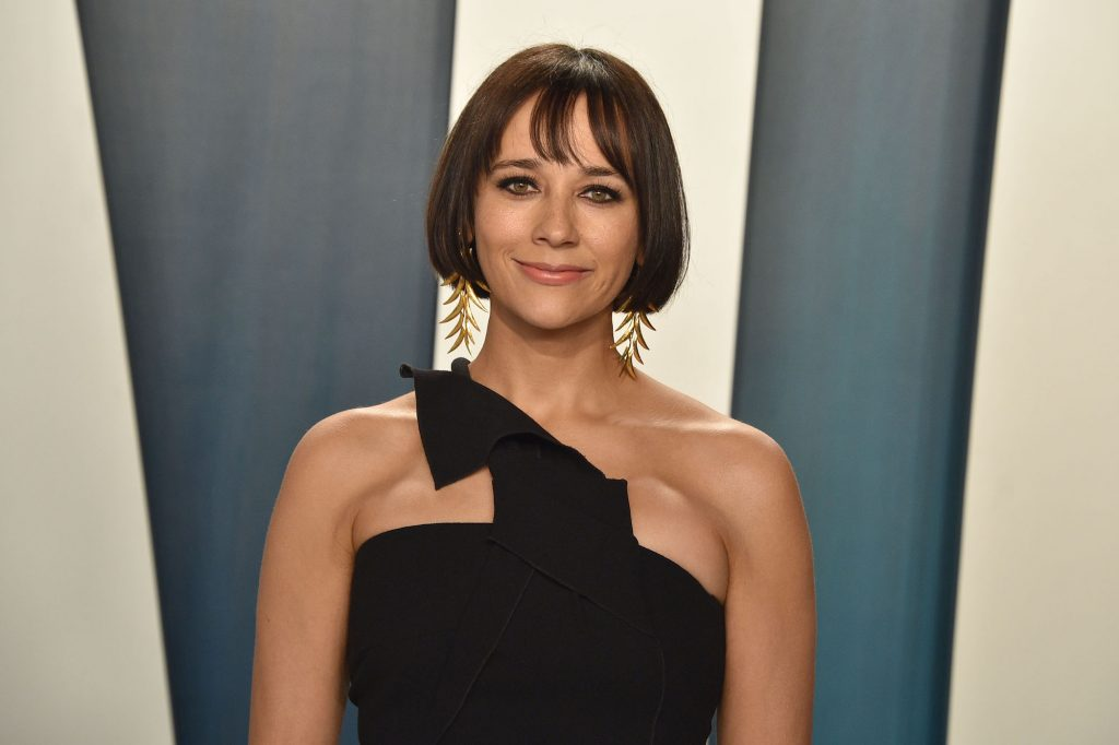 Rashida Jones smiling in front of a blue and white background
