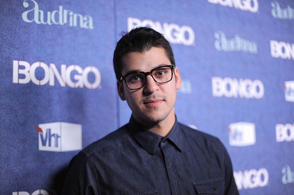 Rob Kardashian wearing glasses in front of a blue background with repeating logo