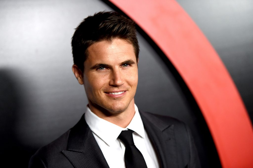 Robbie Amell smiling at the camera in front of a black and red background