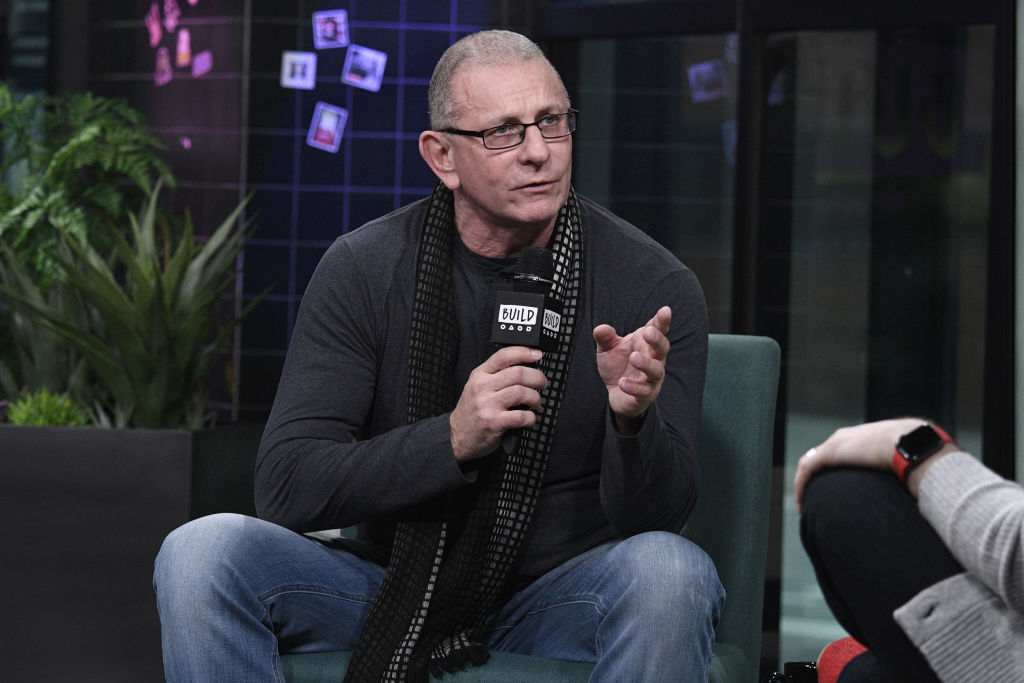 Robert Irvine holding a microphone, seated, talking