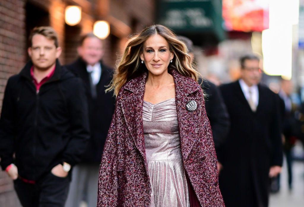 Sarah Jessica Parker smiling, walking down a NYC street