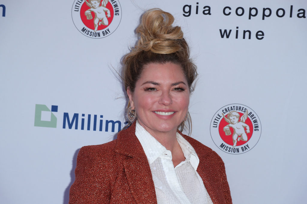 Shania Twain smiling in front of a white background with repeating logos