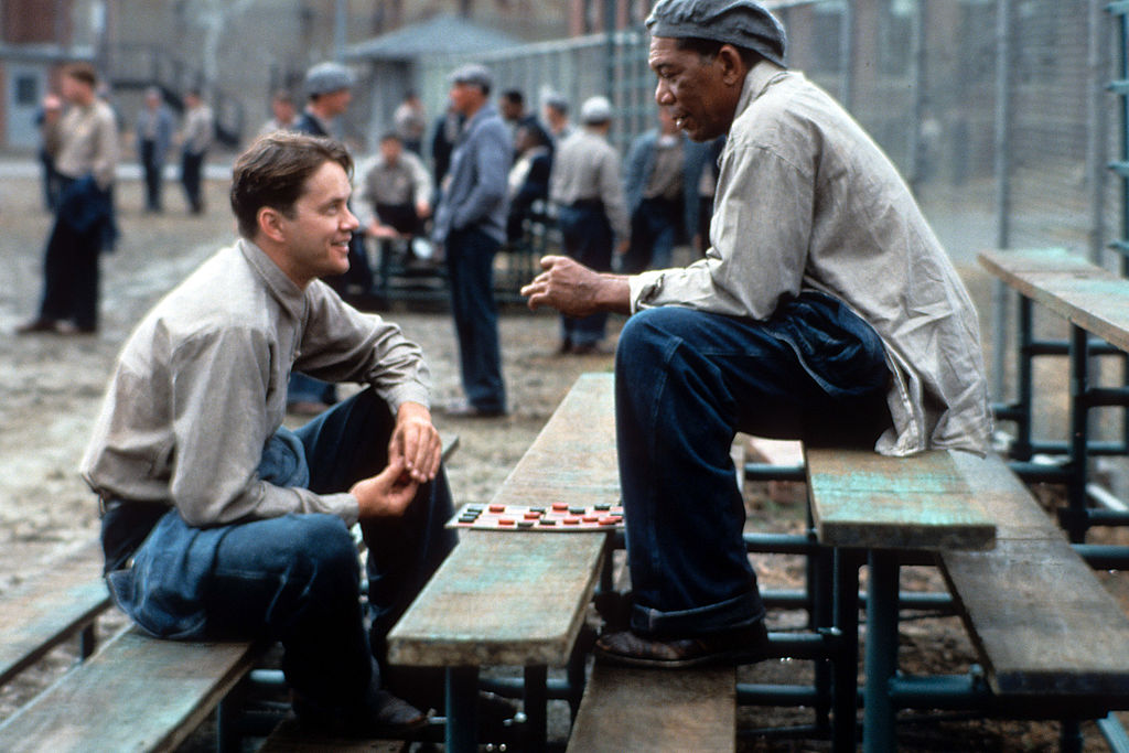 Tim Robbins and Morgan Freeman sitting outside on the benches playing checkers and talking in a scene from the film 'The Shawshank Redemption'
