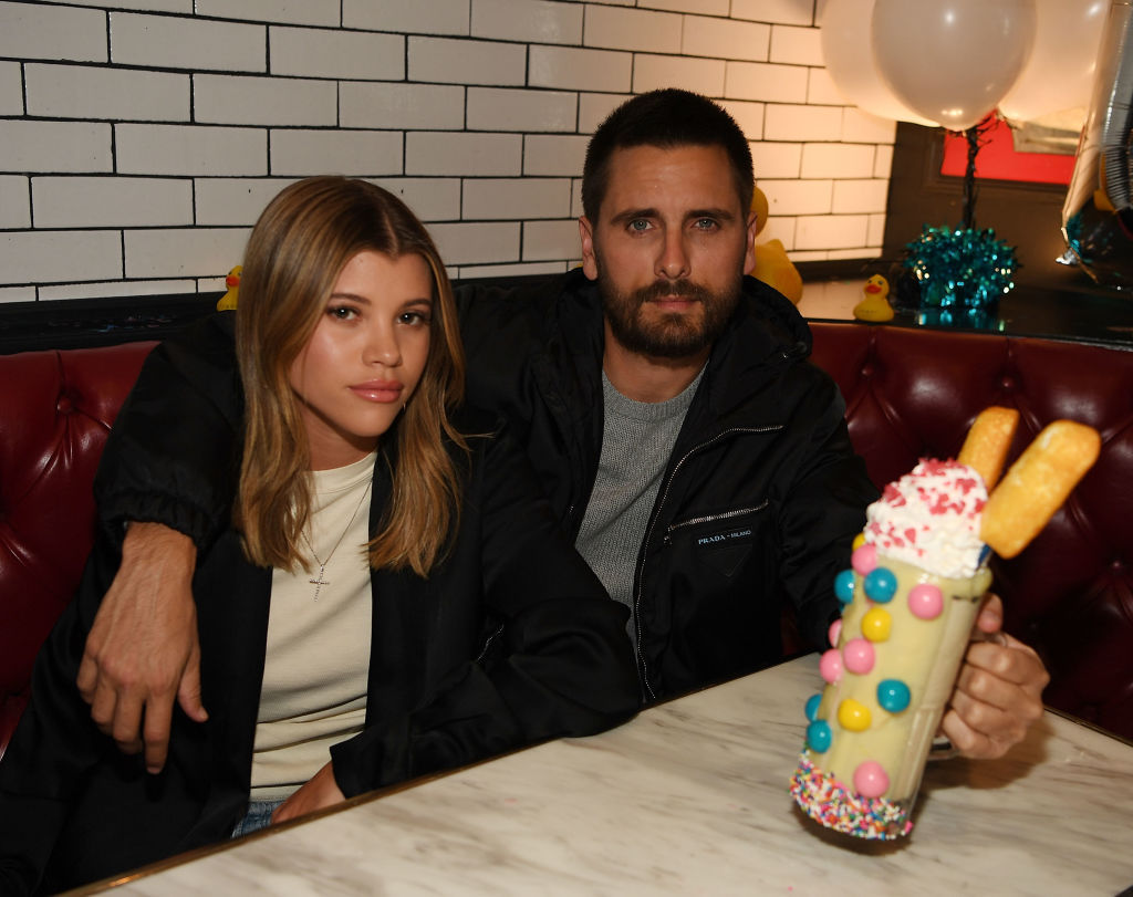 Sofia Richie and Scott Disiskc sitting close together at a dinner table