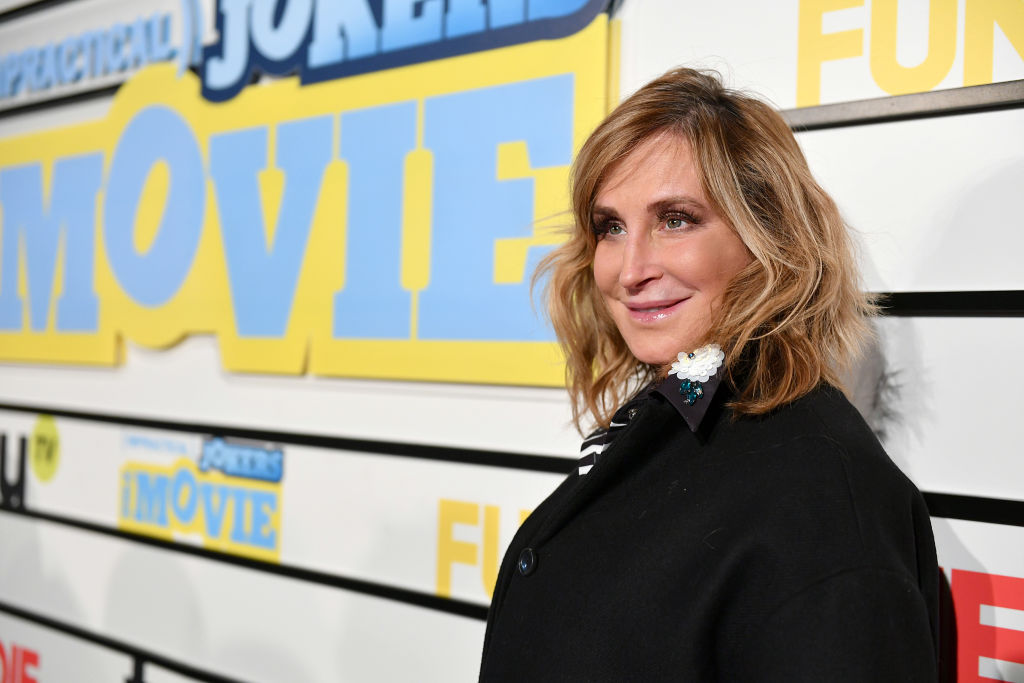 Sonja Morgan smiling in front of a repeating background