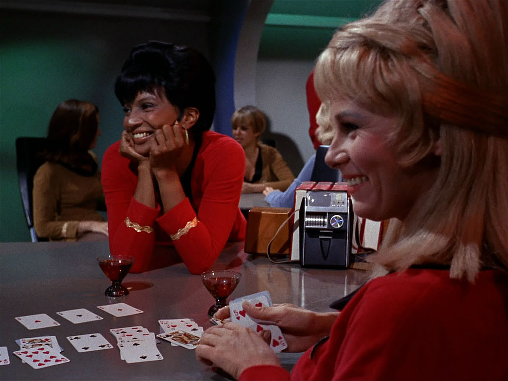 Nichelle Nichols as Lieutenant Uhura, sitting at a card table with drinks, smiling