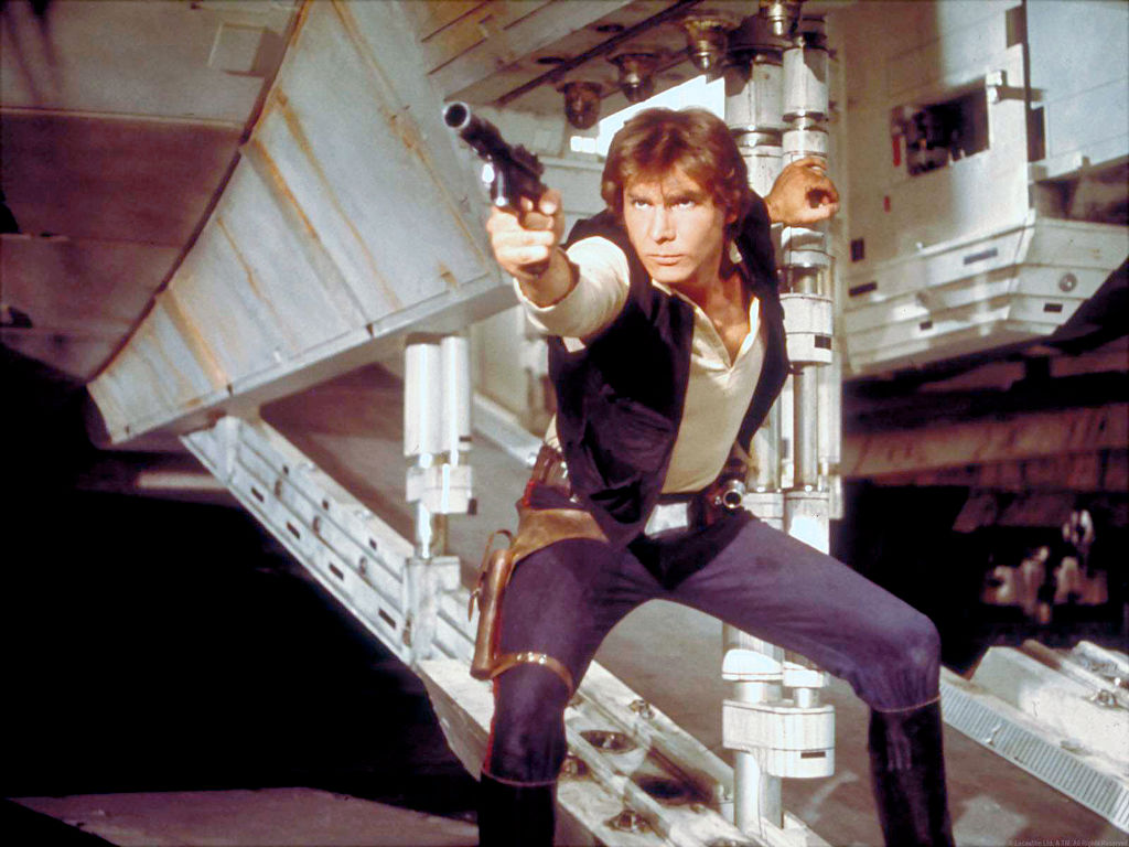 Harrison Ford as Hans Solo on set of 'Star Wars' pointing a gun to the side of the camera