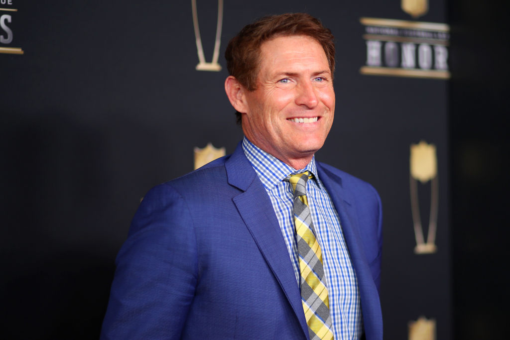 Steve Young smiling in front of a repeating background