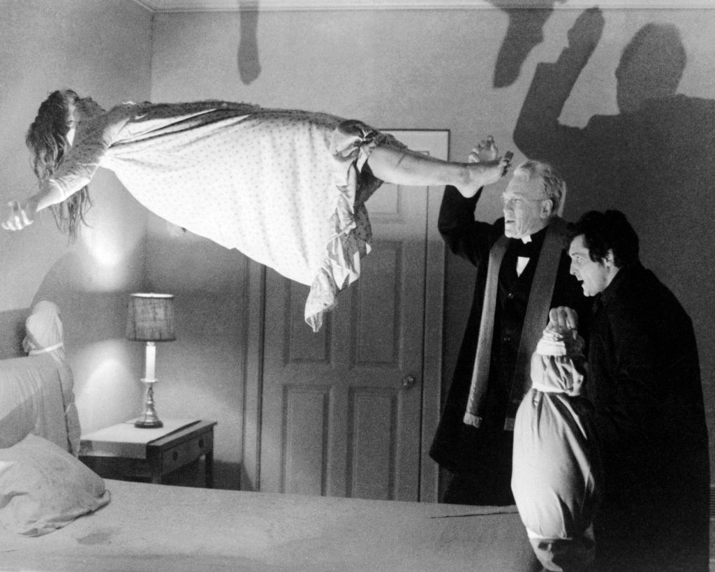 Linda Blair as Regan MacNeil floating in the air, Max von Sydow as Father Merrin, and Jason Miller as Father Karras
