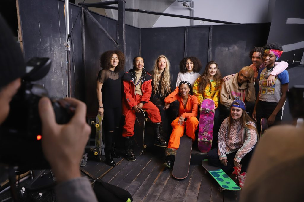 The Skate Kitchen members smiling on a set, holding skateboards