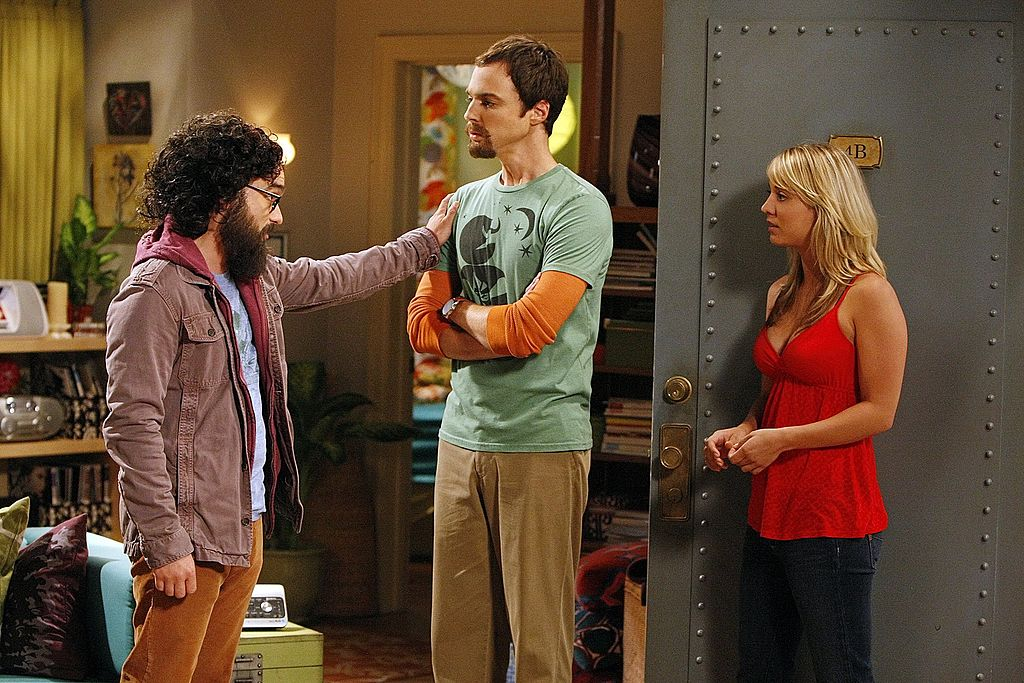Leonard Hofstader (Johnny Galecki, left) tries to comfort an upset Sheldon Cooper (Jim Parsons) with Penny (Kaley Cuoco) standing by