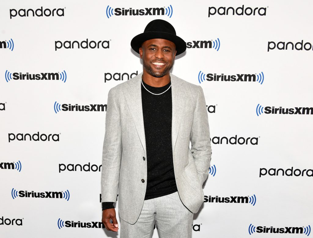 Wayne Brady smiling in front of a repeating background