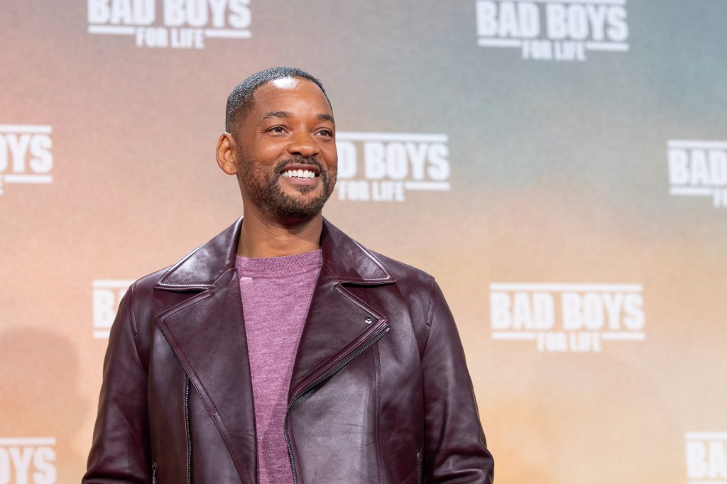 Will Smith smiling, looking away from the camera, wearing a dark red leather jacket